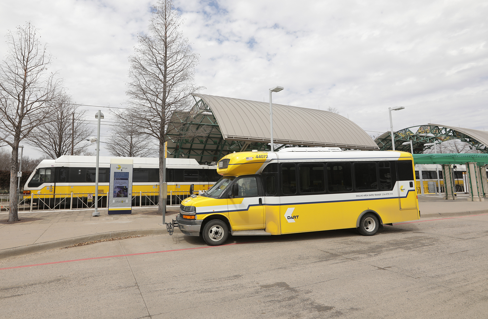 DART small bus and light rail train at LBJ Central Station