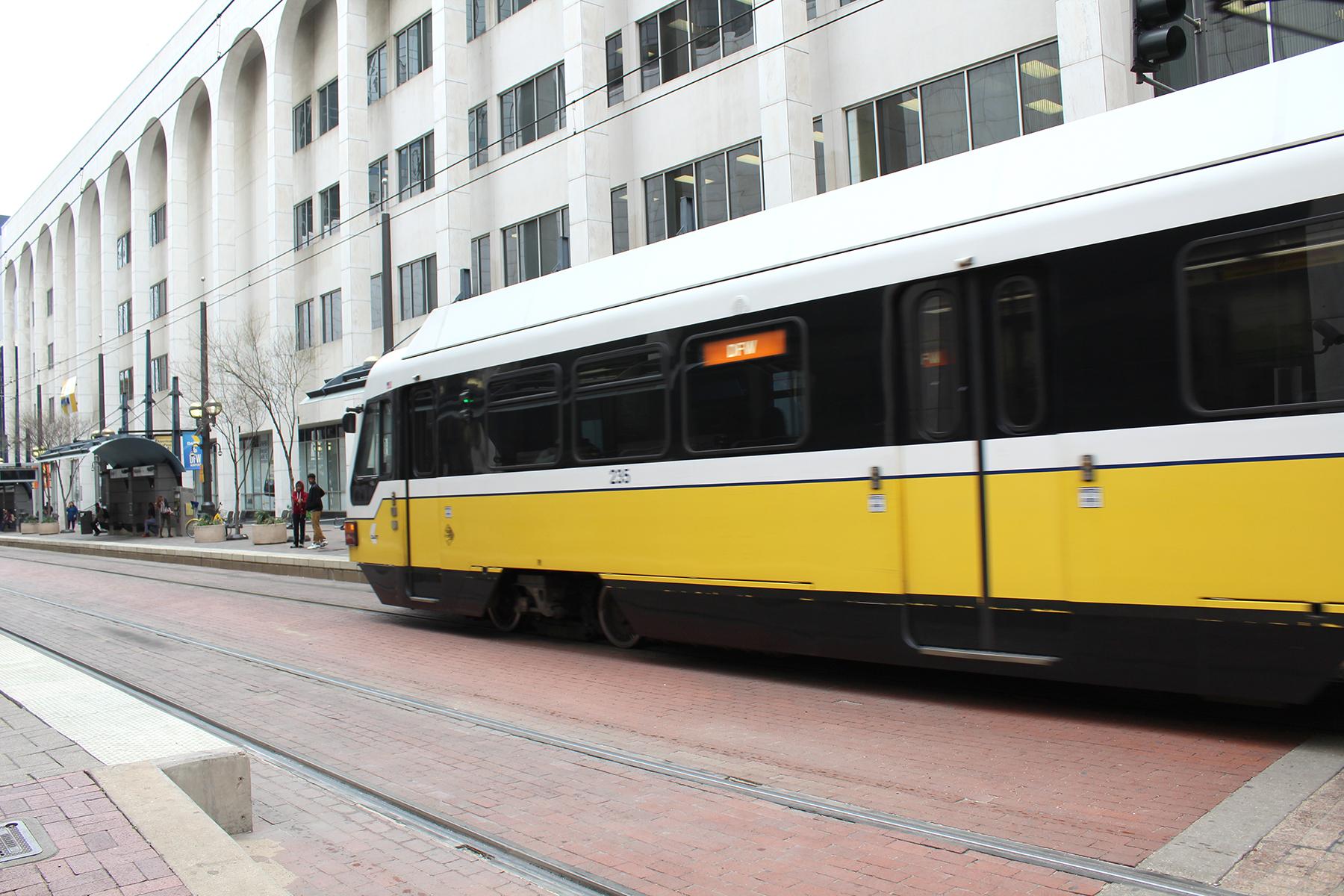 A DART Orange Line train travels by Akard Station in Dallas.