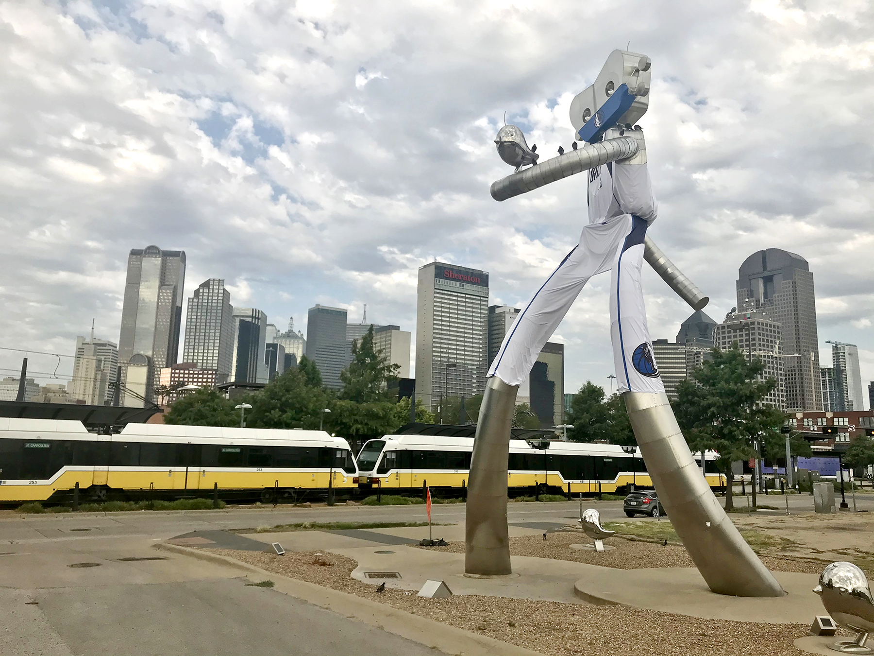 A DART train passes by Deep Ellum Station next to The Traveling Man sculpture in Dallas.